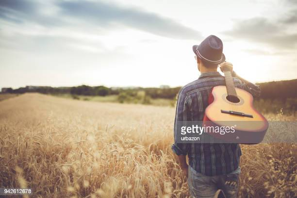 man walking through the wheat field with guitar on back. - acoustic music stock pictures, royalty-free photos & images