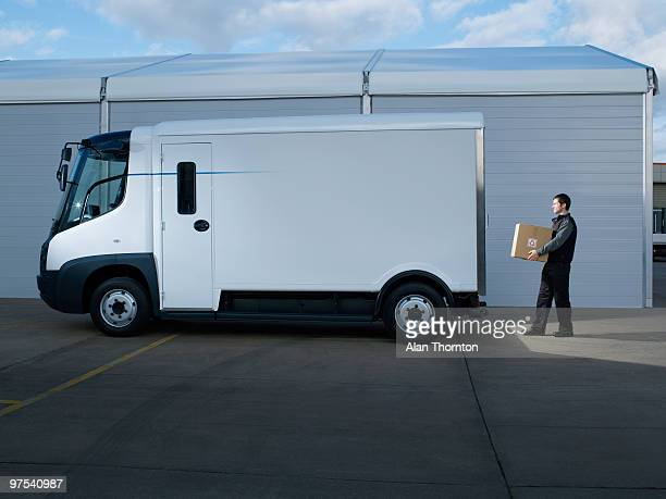 man walking to back of electric van with box - white van stock photos and pictures