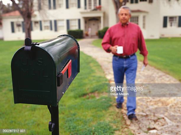 man walking to mailbox in garden - mailbox stock pictures, royalty-free photos & images
