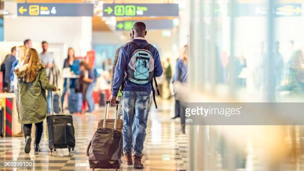 Man walking to the airport gate with his suitcase