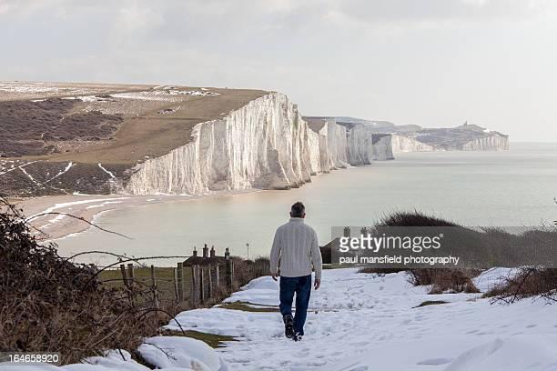Man walking towards dramtic coastline