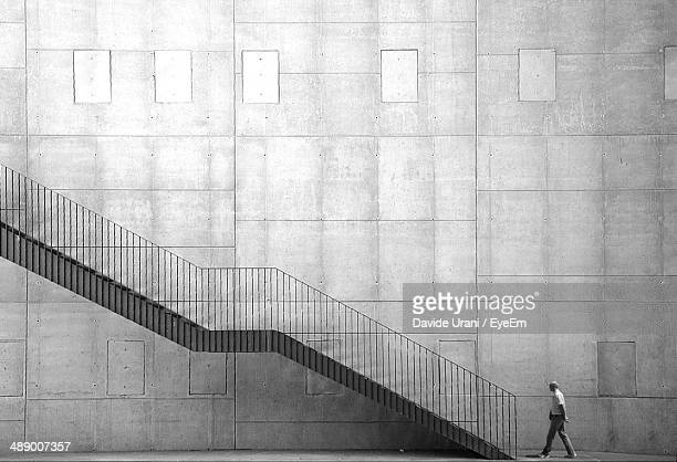 Man walking towards stairs against wall