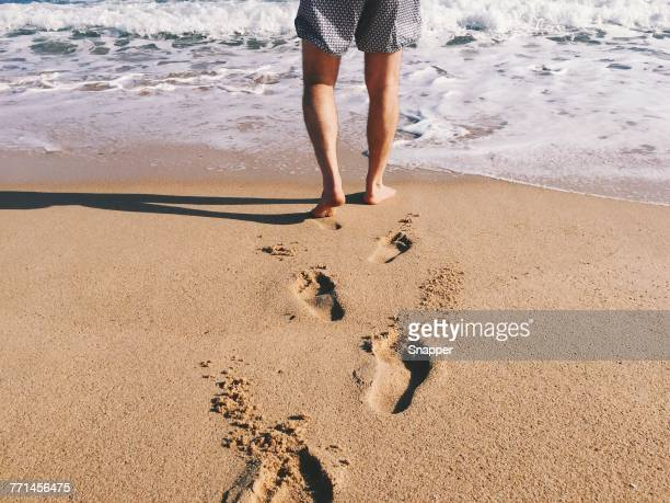 Man walking towards the ocean surf