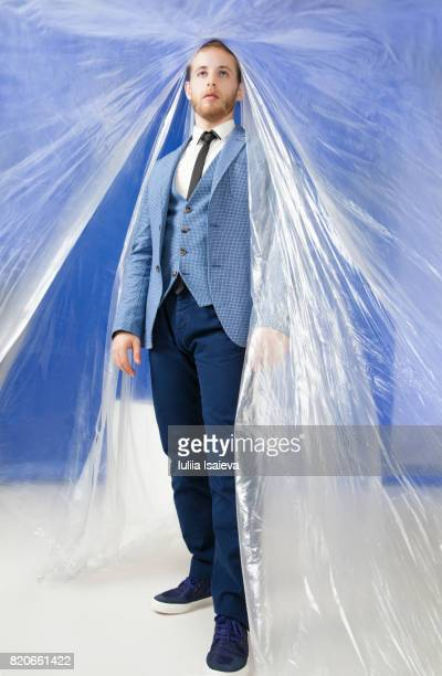 man walking under plastic foil - man wrapped in plastic stock pictures, royalty-free photos & images