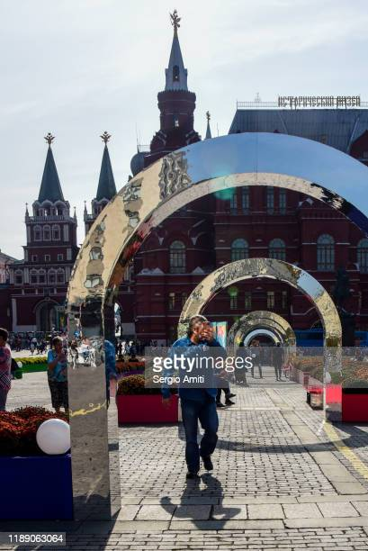 man walking under steel arches in red square - sergio amiti stock pictures, royalty-free photos & images