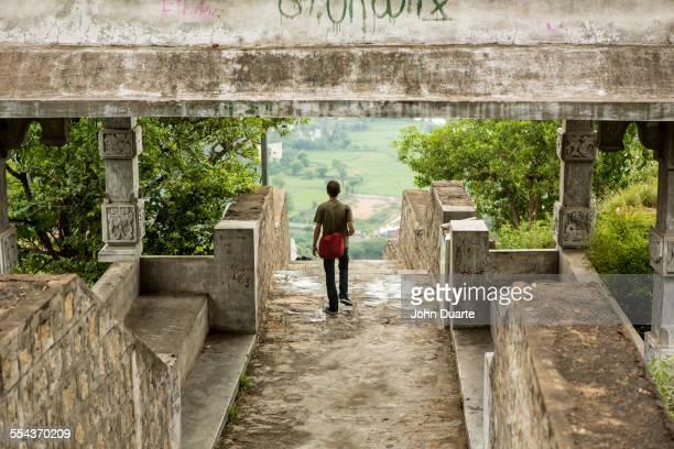 Man walking under stone walkway