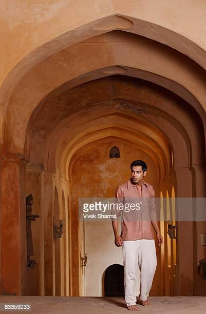 man walking up arched hallway