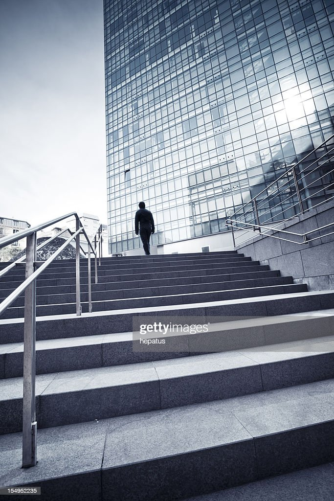 Man Walking Up Concrete Stairs Toward Glass Building High-Res Stock ...