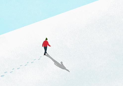 Man walking up snowy slope - gettyimageskorea