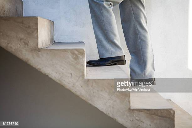 Man walking up staircase, side view, cropped