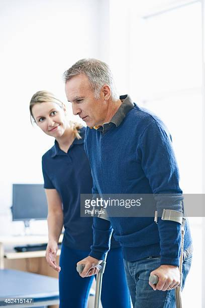 Man walking using crutches, guided by therapist