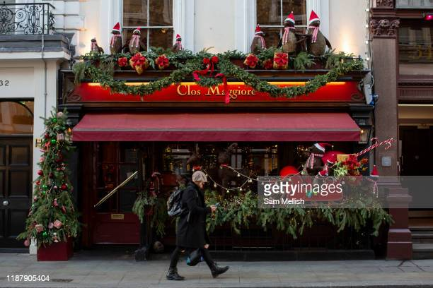 A man walking whilst looking at his mobile phone as he walks past Clos Maggiore resturant at Covent Garden on the 3rd December 2019 in London in the...