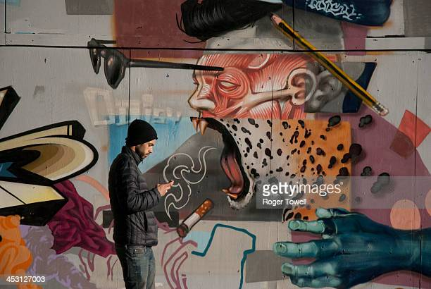 Man walking, whilst using a mobile phone, in front on colourful street art, in central London.