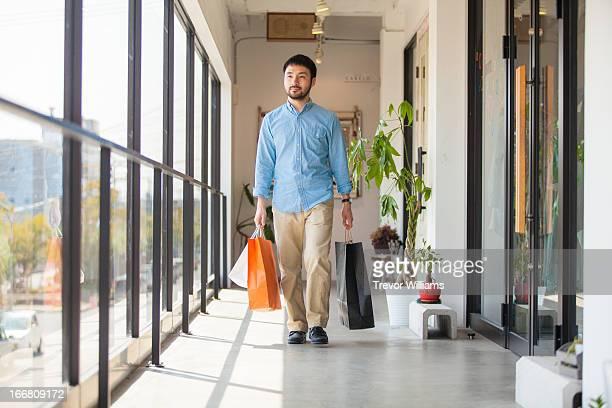a man walking wiht shopping bags - mid adult men imagens e fotografias de stock