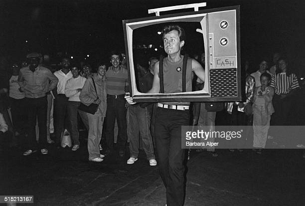 A man walking with a cutout of a TV set during a Halloween parade in Greenwich Village New York City 31st October 1981