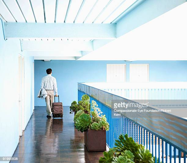 man walking with a rolling suitcase - compassionate eye foundation stock pictures, royalty-free photos & images