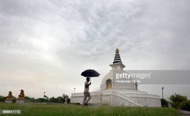 A man walking with an umbrella in a cloudy morning at replica of Shanti Stupa on May 22 2017 in New Delhi India Rain in Delhi brings mercury 10...