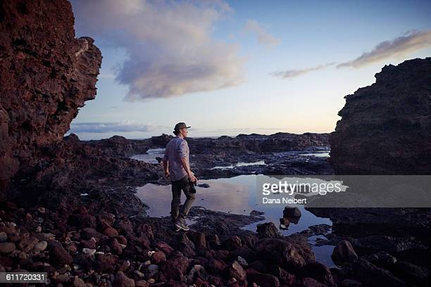 Man walking with camera on lava rocks