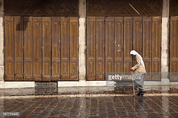Man walking with cane in the street of Aleppo.