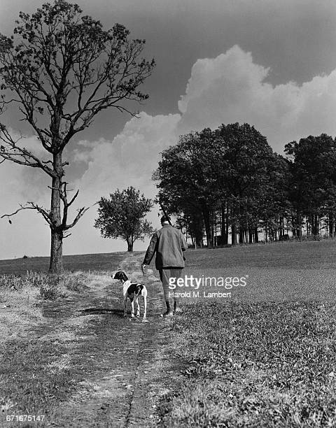 man walking with dog and holding rifle  - {{relatedsearchurl(carousel.phrase)}} stock pictures, royalty-free photos & images