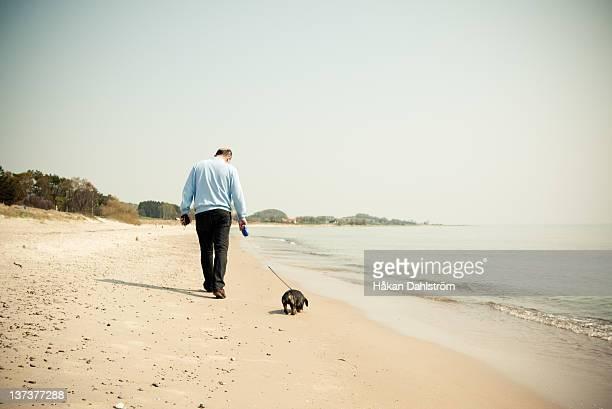 Man walking with dog at beach
