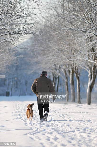 Hombre caminando con el perro en el parque de invierno