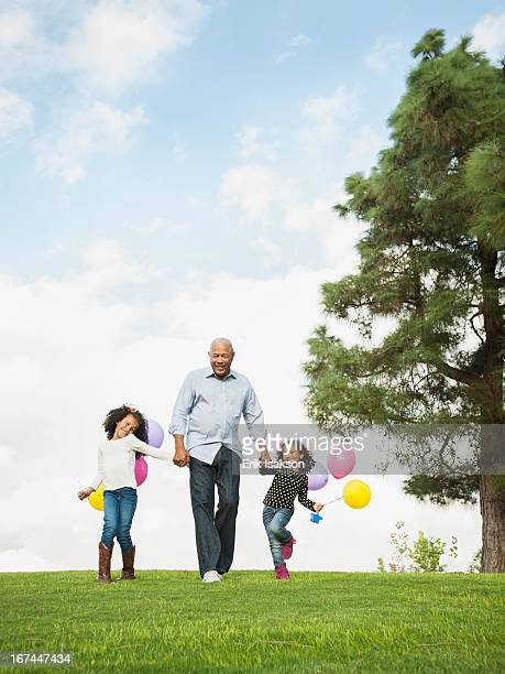 Man walking with granddaughters in park