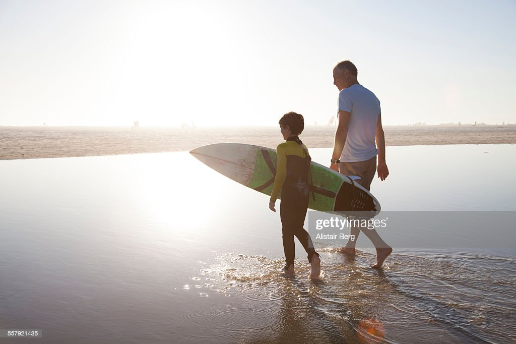 Man walking with grandson carrying surf board : Stock-Foto