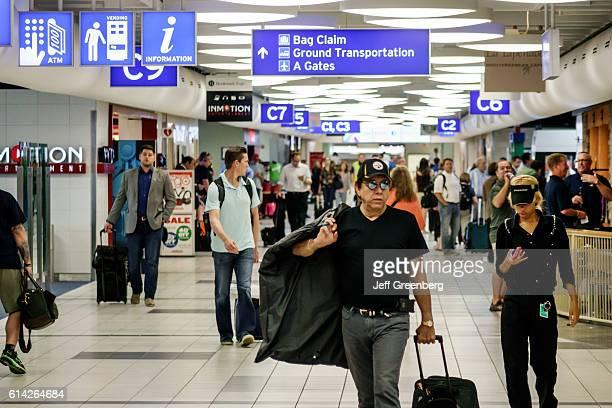 A man walking with his carryon luggage in LambertSt Louis International Airport