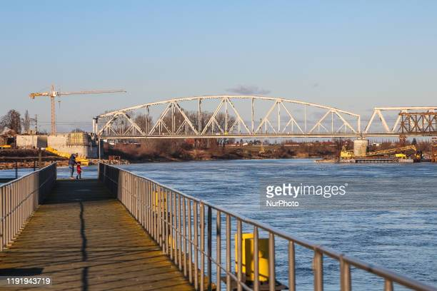 Man walking with his daughter by the pier on the Vistula river bank is seen in Tczew Poland on 5 January 2020