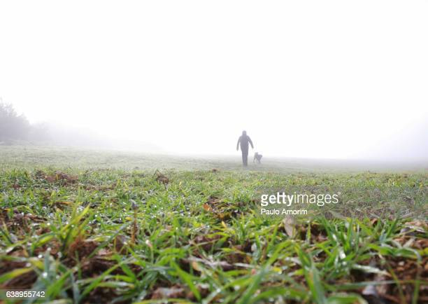 A man walking with his dog during a foggy day
