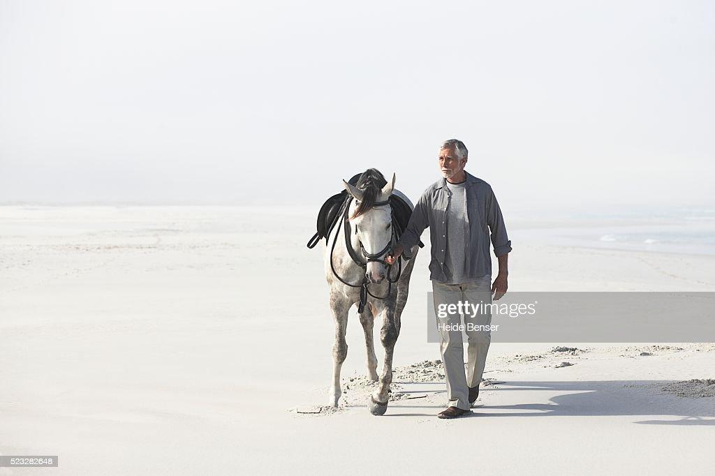 Man walking with horse : ストックフォト