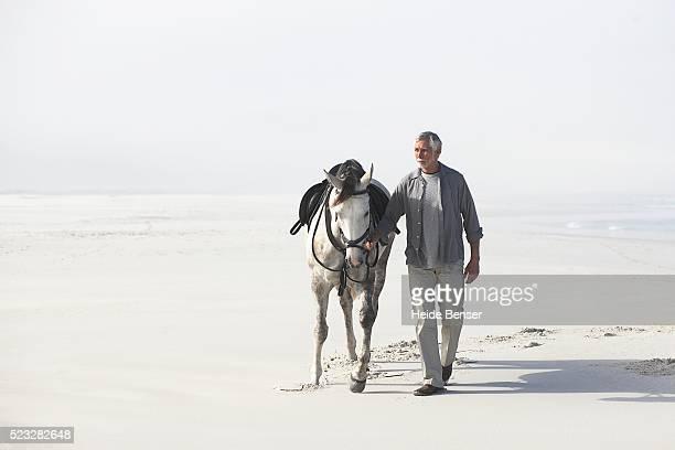 man walking with horse - 接近する ストックフォトと画像