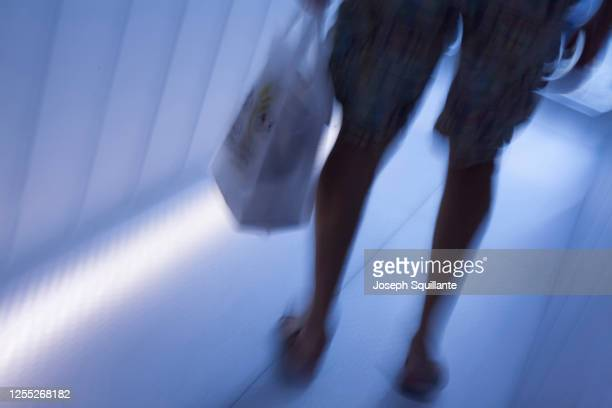 man walking with shopping bag in blue blur - joseph squillante stock pictures, royalty-free photos & images