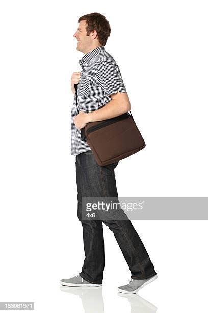 uomo che cammina con una borsa a tracolla - maniche corte foto e immagini stock