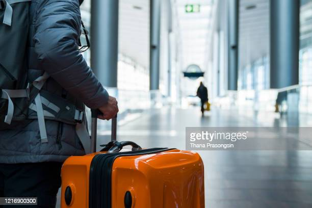 man walking with suitcase at airport terminal - travel stock pictures, royalty-free photos & images