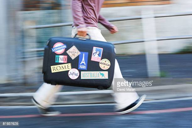 Man walking with suitcase with stickers from countries