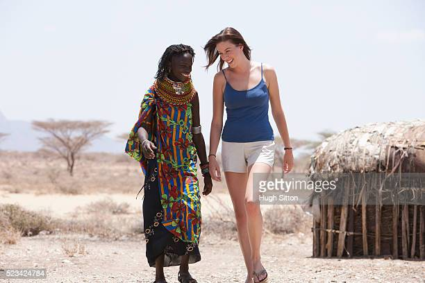man walking with tribeswoman - hugh sitton stock pictures, royalty-free photos & images