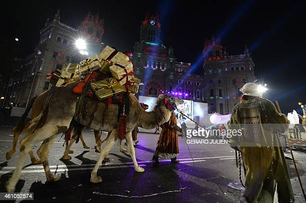 A man walks a camel carrying presents during the Three Kings parade in Madrid on January 5 2015 Every year on January 5 children and parents can see...