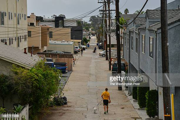 A man walks a dog as a woman bounces from trash bin to trash bin in the alley just west of Louisiana Street one of the locations where James...