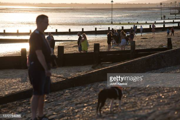 A man walks a dog as people visit the beach at sunset on Chalkwell beach on September 13 2020 in Southend on Sea England Parts of the UK are expected...