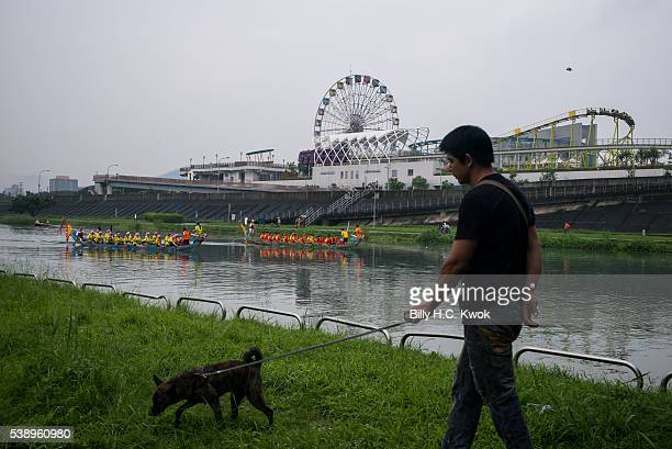 A man walks a dog during the dragon boat race celebrating the Dragon Boat Festival on June 9 2016 in Taipei Taiwan Cities across Asia celebrated...