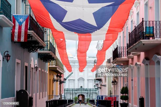 TOPSHOT A man walks a dog in front of the Governor's mansion in Old San Juan Puerto Rico on April 7 2020 On March 15 Puerto Rico Governor Wanda...