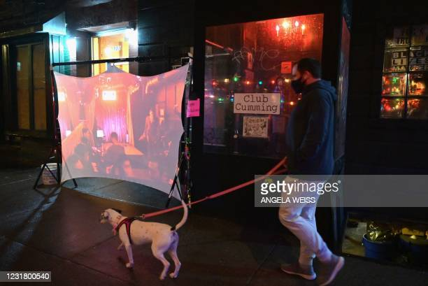 """Man walks a dog past an outdoor projection during the """"Pandemic Burlesque"""" show presented by Tallulah Talons at Club Cumming on March 18, 2021 in New..."""