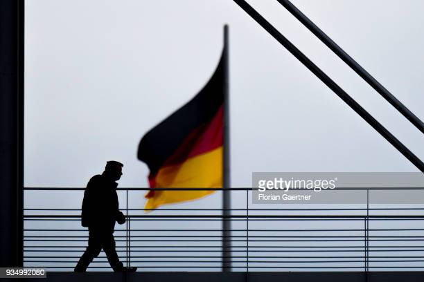 Man walks across a bridge in front of the waving german flag on March 20, 2018 in Berlin, Germany.