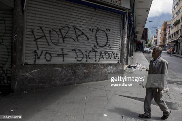 A man walks across a closed shop in Caracas Venezuela 26 July 2017 'Hour 0 No Dictatorship' is written on the blinds With a 48hours general strike...