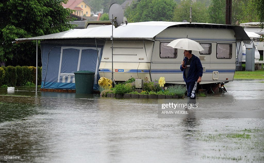 A man walks across a flooded camping site in Bad Koetzting, southeastern Germany on June 3, 2010. Many rivers and streets are flooded in southern Germany due to heavy rainfalls during the last days.