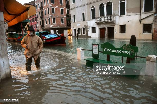 """Man walks across a flooded canal on December 8, 2020 in Venice following a high tide """"Alta Acqua"""" event following heavy rains and strong winds, and..."""