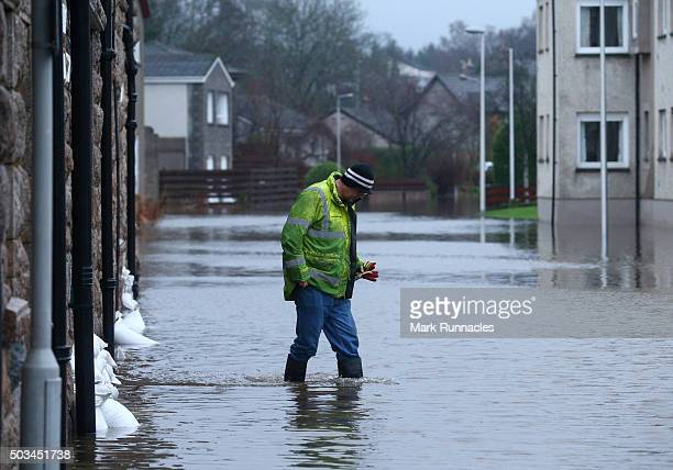 A man walks across a heavy flooded streets in Aboyne after more heavy rain caused a local burn to burst its banks on January 5 2016 in Aboyne United...