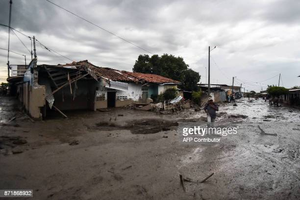 A man walks across a muddy street after a mudslide due to heavy rains affected Corinto in Cauca department southwest Colombia on November 8 2017 The...